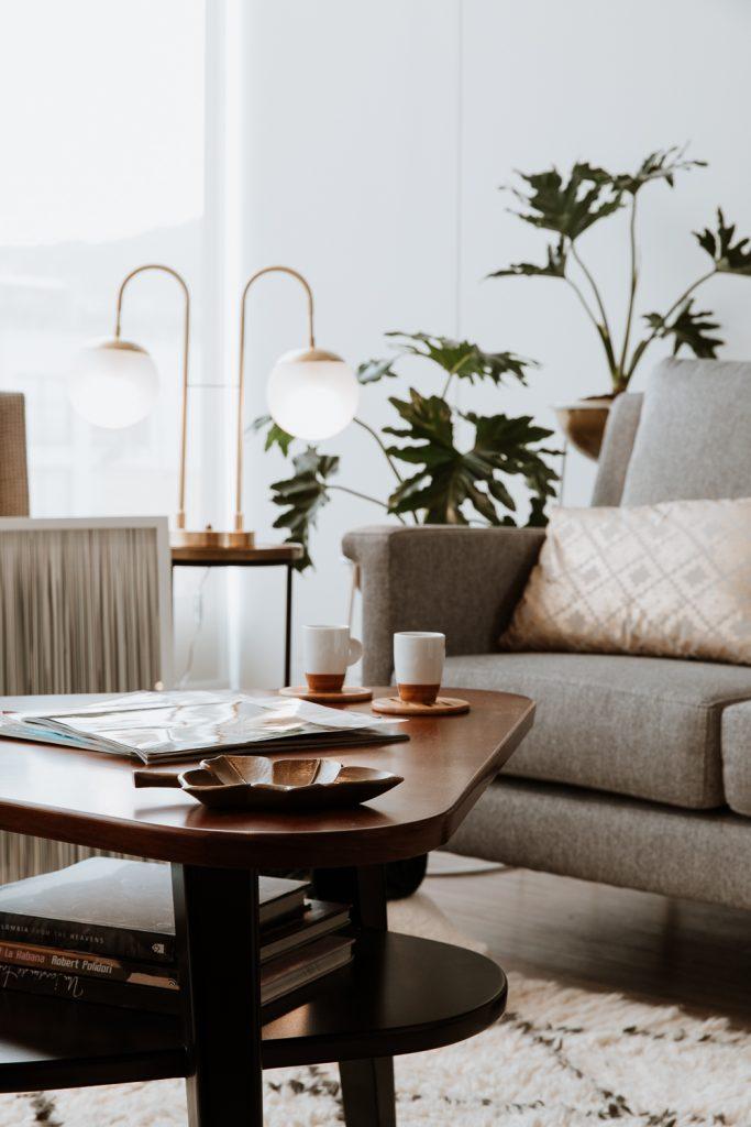 Mesa de centro con lámpara industrial, sofá y cojín decorativo